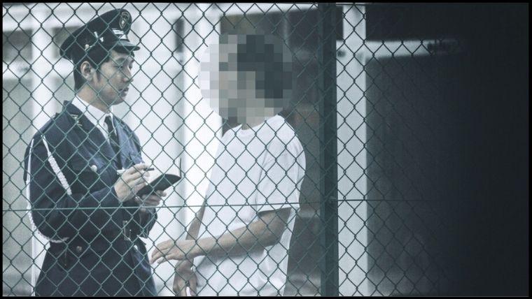 路地裏で警察官に職質される男性